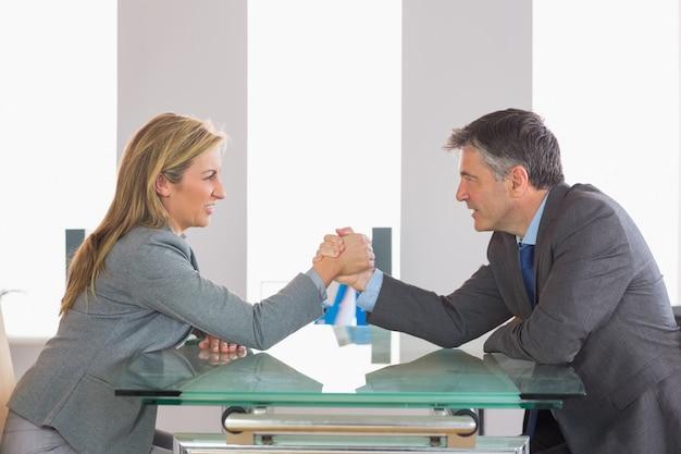 Zwei wirtschaftler, die einen showdown haben, der um eine tabelle sitzt
