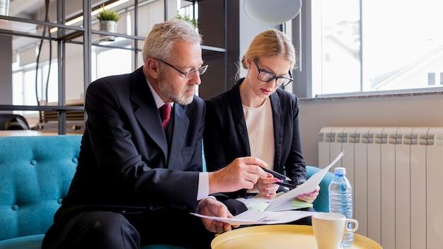 Zwei wirtschaftler, die vertrag im büro besprechen