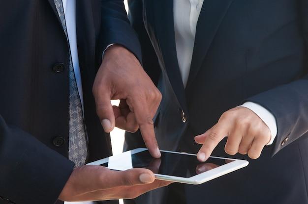 Zwei wirtschaftler, die zusammen tablette verwenden