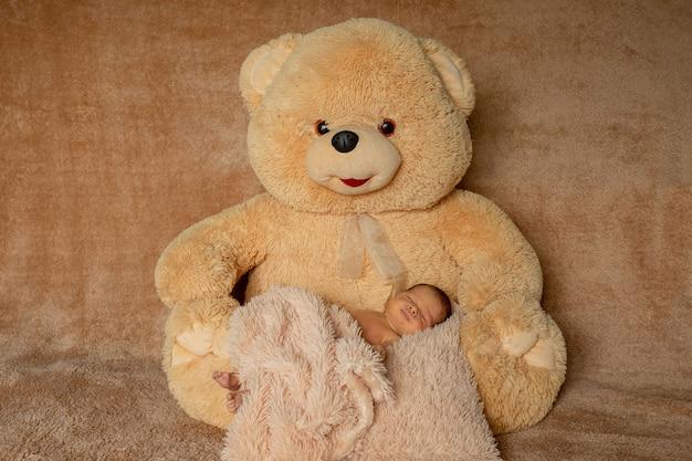 Zwei wochen altes neugeborenes, das auf teddybär schläft.
