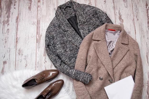 Zwei wollmäntel, braune lackschuhe auf einem weißen fell, weißes leeres blatt, ein hölzernes. mode. ansicht von oben