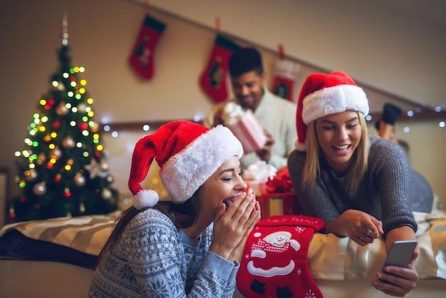 Zwei wunderschöne attraktive mädchen mit weihnachtsmützen, die über mobilen text lachen