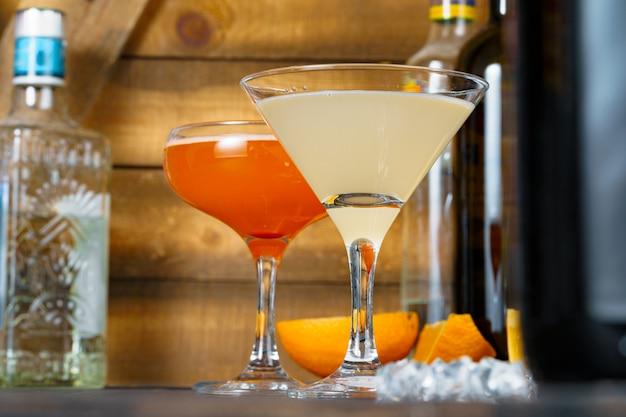 Zwei wunderschöne cocktails serviert auf einem hölzernen bartresen