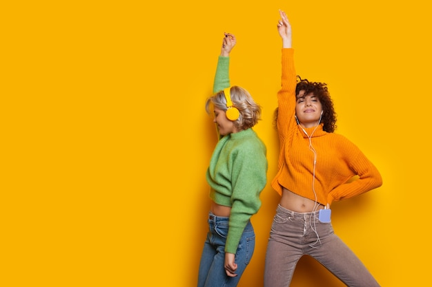Zwei wunderschöne kaukasische mädchen tanzen auf gelbem grund, während sie musik über kopfhörer hören