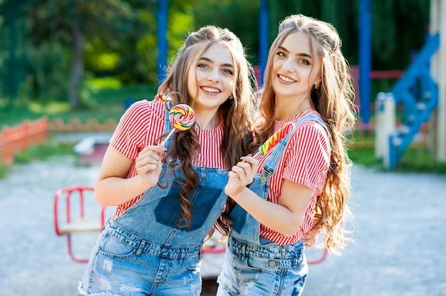 Zwei wunderschöne zwillingsmädchen, die sich in jeansoveralls mit lutschern umarmen und lachen