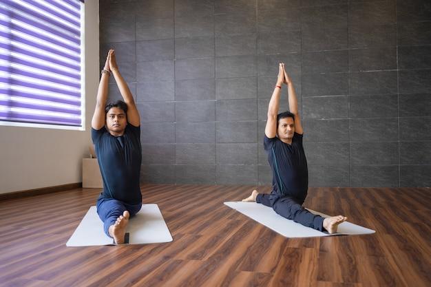 Zwei yogis, die affengotthaltung in der turnhalle tun