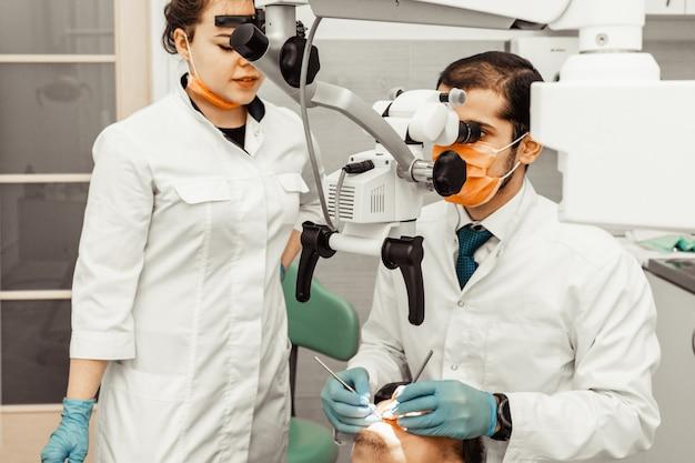 Zwei zahnärzte behandeln einen patienten. berufsuniform und ausrüstung eines zahnarztes. gesundheitswesen ausstattung eines arztarbeitsplatzes. zahnheilkunde