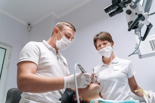 Zwei zahnärzte untersuchen die zähne des patienten auf die behandlung.