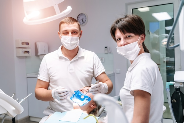 Zwei zahnärzte untersuchen die zähne des patienten für die weitere behandlung