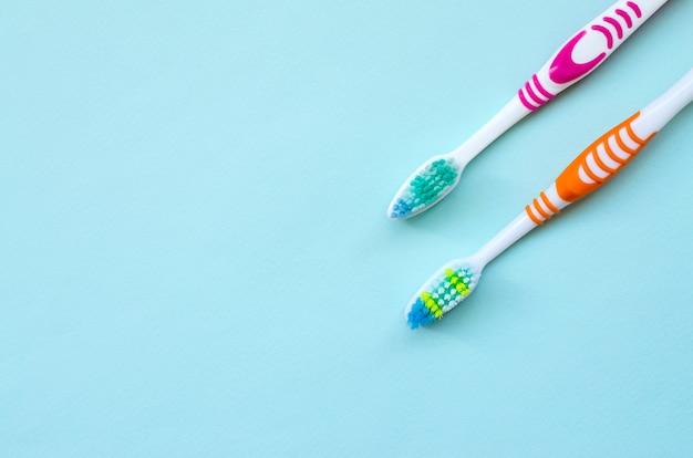 Zwei zahnbürsten liegen auf einem blauen pastellhintergrund. draufsicht flach liegend. minimales konzept