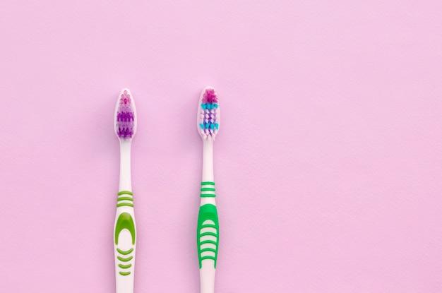 Zwei zahnbürsten liegen auf einem pastellrosa