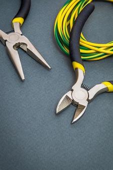 Zwei zangenwerkzeuge und drähte für einen elektriker im dunkeln werden vom master zur reparatur von elektrizität verwendet