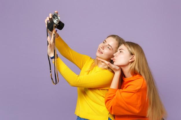 Zwei zarte blonde zwillingsschwestern mädchen, die selfie auf retro-vintage-fotokamera machen und luftkuss einzeln auf violettblauer wand senden. menschen-familien-lifestyle-konzept.