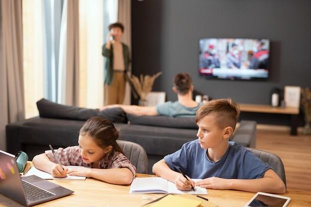 Zwei zeitgenössische schulkinder sitzen am tisch vor dem laptop, machen sich notizen in heften und hören ihrem lehrer während des online-unterrichts zu