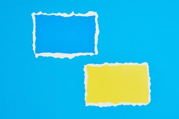 Zwei zerrissene papier zerrissene randblätter auf blauem hintergrund. vorlage mit einem stück farbpapier
