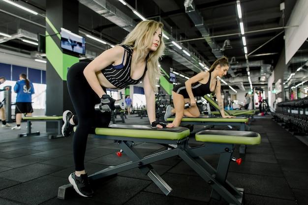 Zwei ziemlich athletische frauen, die muskeln mit hanteln aufpumpen. fitness-mädchen, die mit langhantel im fitnessstudio trainieren