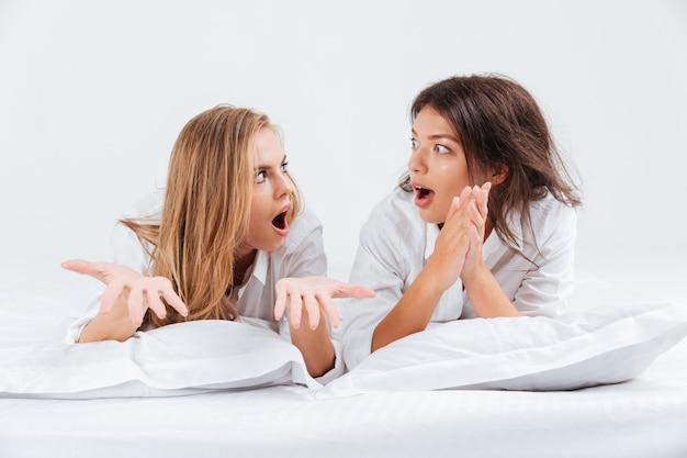 Zwei ziemlich überraschte frauen in hemden, die mit kissen auf einem weißen bett liegen und sich ansehen