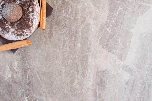 Zwei zimtstangen, ein donut und ein tannenzapfen auf marmor.