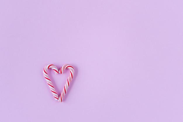 Zwei zuckerstangen, die ein herz auf rosa hintergrund machen. minimaler valentinstag oder muttertagkonzept mit kopienraum