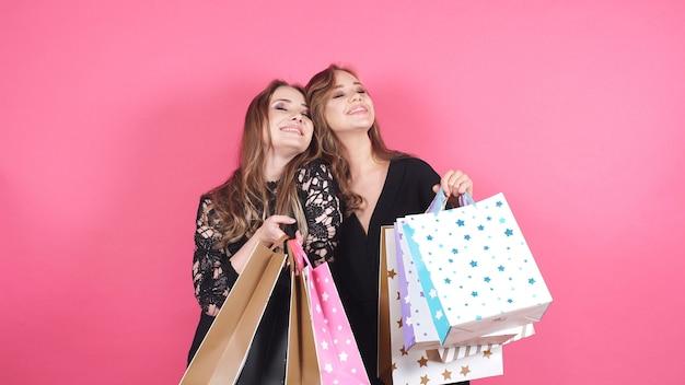 Zwei zufriedene frauen genießen das einkaufen auf einem isolierten hintergrund