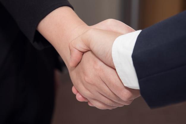 Zwei zuversichtlich geschäftsmann und geschäftsfrau händeschütteln