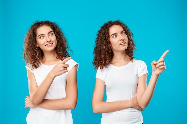 Zwei zwillinge der frau lächeln und zeigen mit den fingern über blau.