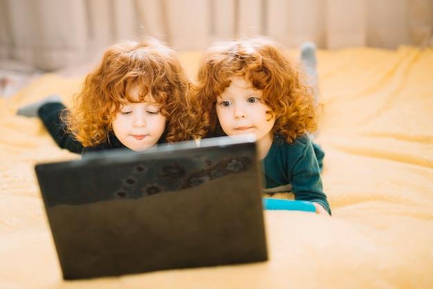 Zwei zwillinge, die auf dem bett betrachtet laptop liegen