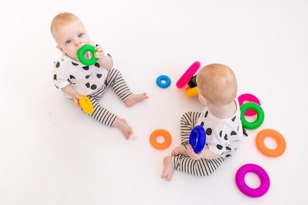 Zwei zwillingsbabys spielen auf einem weißen isolierten hintergrund, frühe entwicklung von kindern bis zu einem jahr alt, ein ort für text