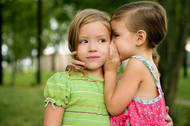 Zwei zwillingsmädchen der kleinen schwester flüstern im ohr