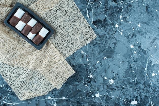 Zweifarbige bonbons auf einer holzplatte auf einer tischdecke, auf dem blauen tisch.