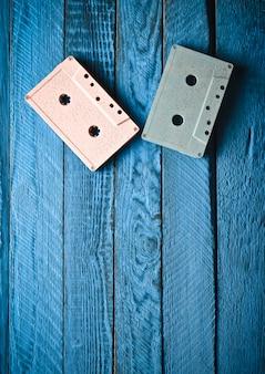 Zweifarbige pastell-audiokassette auf einem blauen holztisch. draufsicht, minimalistischer trend