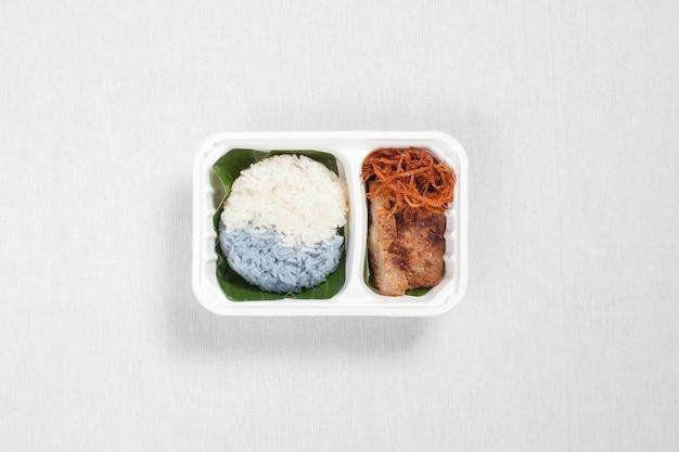 Zweifarbiger klebreis mit gegrilltem schweinefleisch und zerkleinertem schweinefleisch in einer weißen plastikbox, auf einer weißen tischdecke, einer lebensmittelbox und thailändischem essen.