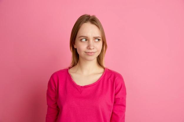 Zweifel, unsicherheit. porträt der kaukasischen jungen frau auf rosa studio