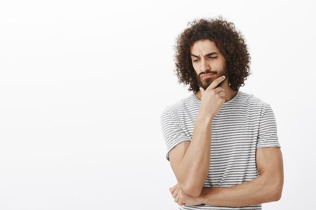 Zweifelhaft fokussierter erwachsener bärtiger mann mit dunkler haut und afro-frisur, händchen haltend am kinn, blick nach unten und stirnrunzeln beim nachdenken oder zögern