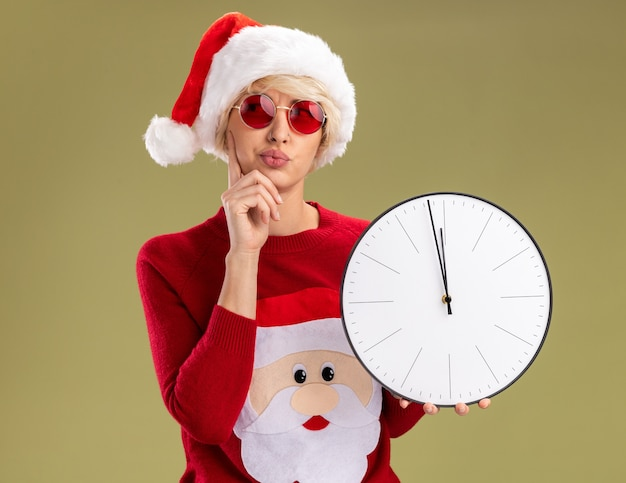 Zweifelhafte junge blonde frau, die weihnachtsmütze und weihnachtsmannpullover des weihnachtsmannes mit gläsern hält, die uhr halten hand auf kinn halten, das seite lokalisiert auf olivgrünem hintergrund betrachtet