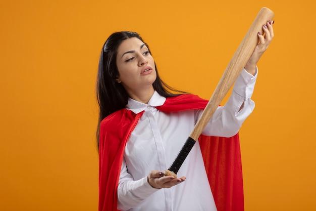 Zweifelhafte junge superfrau, die baseballschläger lokalisiert auf orange wand hält und betrachtet