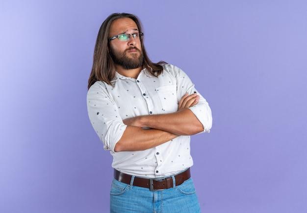 Zweifelhafter erwachsener gutaussehender mann mit brille, der mit geschlossener haltung steht und auf die seite isoliert auf lila wand mit kopierraum schaut