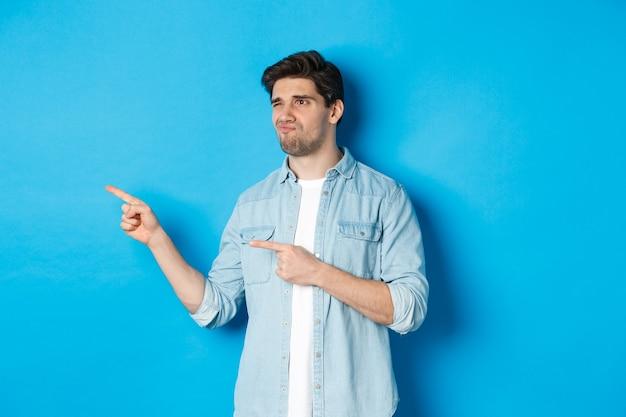 Zweifelhafter erwachsener mann, der mit dem finger auf die beförderung zeigt und unsicher aussieht, enttäuscht das gesicht verzieht und vor blauem hintergrund steht