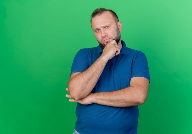 Zweifelhafter erwachsener slawischer mann, der hände unter ellbogen und auf kinn lokalisiert auf grüner wand mit kopienraum setzt