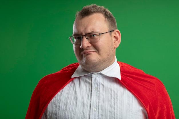 Zweifelhafter erwachsener superheldenmann im roten umhang, der brille trägt, die front lokal auf grüner wand betrachtet