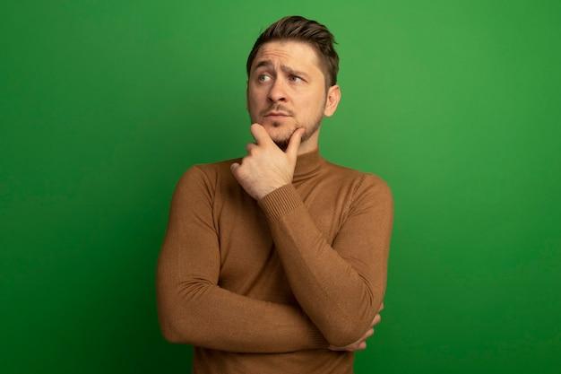 Zweifelhafter junger blonder gutaussehender mann, der das kinn berührt und die seite isoliert auf grüner wand mit kopienraum betrachtet