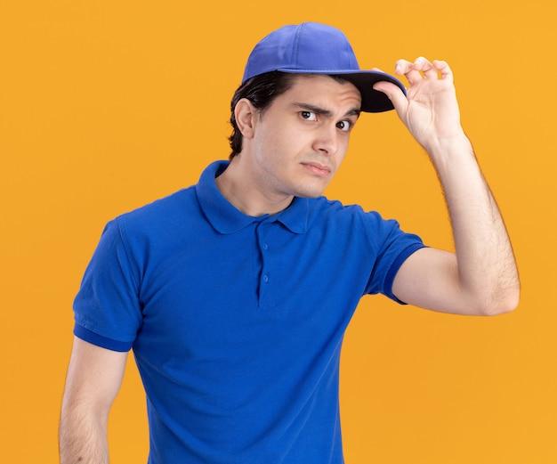 Zweifelhafter junger kaukasischer lieferbote in blauer uniform und mütze, die mütze greift
