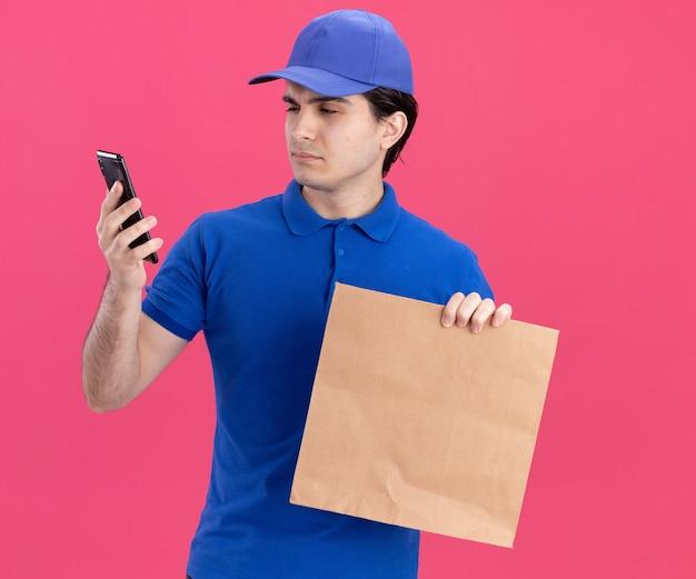 Zweifelhafter junger kaukasischer lieferbote in blauer uniform und mütze mit papierpaket und handy, der auf das telefon schaut