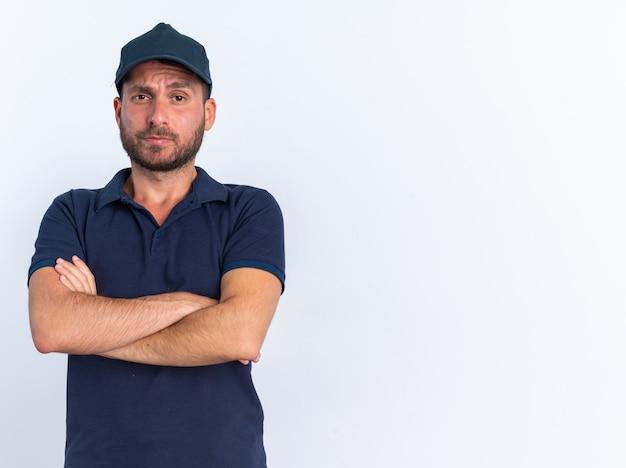 Zweifelhafter junger kaukasischer zusteller in blauer uniform und mütze, der mit geschlossener haltung in die kamera schaut, isoliert auf weißer wand mit kopierraum