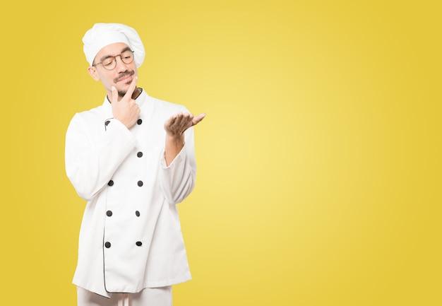 Zweifelhafter junger koch, der etwas mit seiner hand hält