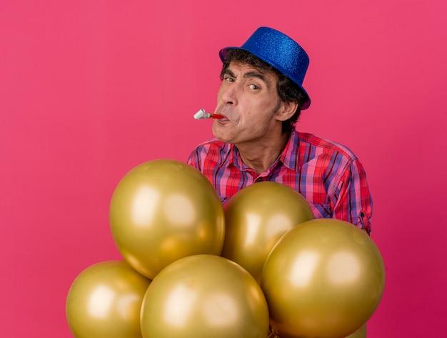 Zweifelhafter parteimann mittleren alters, der parteihut trägt, der hinter luftballons steht, die vorne mit parteigebläse im mund lokalisiert auf purpurroter wand betrachten