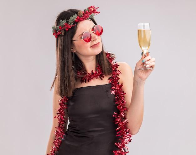 Zweifelhaftes junges hübsches kaukasisches mädchen mit weihnachtskopfkranz und lametta-girlande um den hals mit brille, die ein glas champagner auf weißem hintergrund hält und anschaut