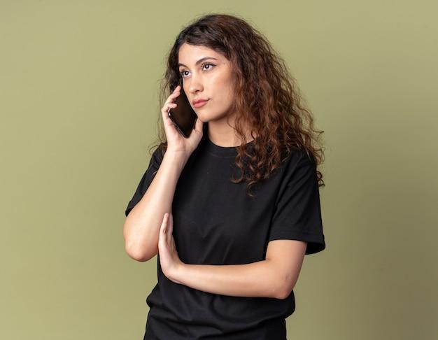 Zweifelhaftes junges hübsches mädchen, das am telefon spricht und die seite isoliert auf olivgrüner wand mit kopienraum betrachtet
