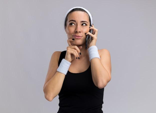 Zweifelhaftes junges hübsches sportliches mädchen mit stirnband und armbändern, das am telefon spricht und die hand am kinn hält, schaut nach oben