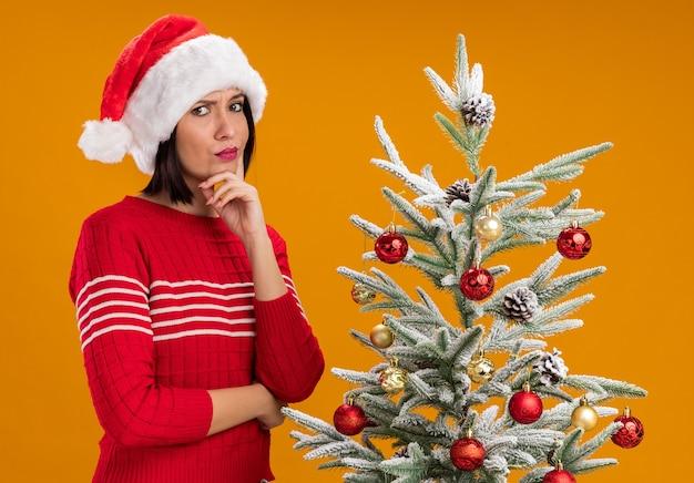 Zweifelhaftes junges mädchen, das weihnachtsmütze trägt, die in der profilansicht nahe verziertem weihnachtsbaum steht, der hand auf kinn hält, das kamera lokalisiert auf orange hintergrund betrachtet